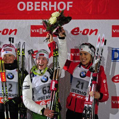Kaisa Mäkäräinen, Daria Domratsheva ja Synnoeve Syllemdal juhlivat palkintokorokkeella.