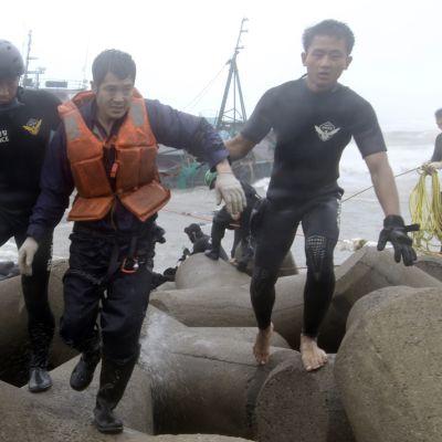 Kaksi rannikkovartijaa kuljettaa kiinalaista kalastajaa turvaan rantautuneelta alukselta.