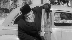 F. E. Sillanpää sovittautuu vaivaloisesti autoon.