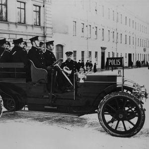 Ett gammalt polisfordon från början av 1900-talet fullastat med poliser på en snöig gata i en stad med höghus.