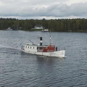 Vit ångbåt åker längs Kajana älv.