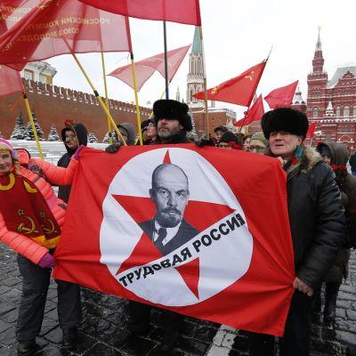 """Punalippuja kantava pieni ihmisjoukko Punaisella torilla. Etummailla on levitettynä lippu, jossa on Leninin kasvokuva, punatähti ja teksti """"työläisten Venäjä""""."""