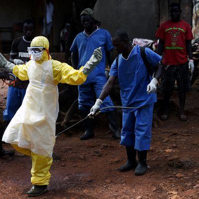 Hoitajat desinfioivat suojavaatteensa siirrettyään ruumiita Freetownissa