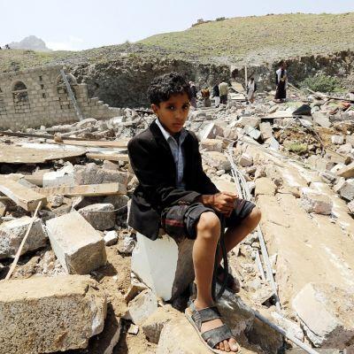 Kiharatukkainen poika istuu raunioiden päällä katsoen surullisena kameraan. Hänellä on yllään tumma takki, ylöskäärityt housut ja sandaalit. Taustalla näkyy aikuisia ja pala pystyyn jäänyttä seinää. Kauempana on vihreä kukkula ja vuoristoista maisemaa.