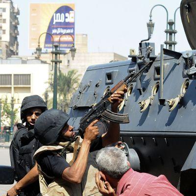 Egyptin turvallisuusjoukkojen sotilaat suojautuvat panssariajoneuvon taakse ja vastaavat al-Fateh-moskeijan minareettiin piiloutuneen sala-ampujan tulitukseen.