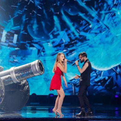 Nainen ja mies lavalla kiiltävän lavastetykin edessä.