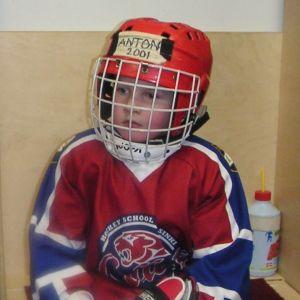 Anton Lundell som cirka femåring. Sitter i omklädningsrummet med hockeyutrustning.