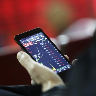 Lähikuva puhelimesta, jonka näytöllä pörssikurssien lukuja ja käyriä.