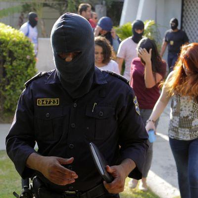 Elsalvadorilaiset poliisit saattavat lakitoimisto Mossack Fonescan työntekijöitä yhtiön tiloista.