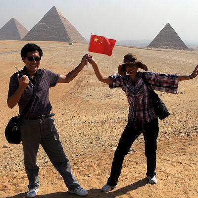 Kiinalainen turistipariskunta poseeraa Gizan pyramidien edustalla.