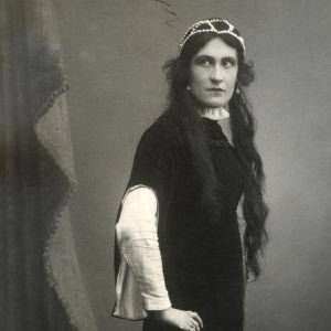 Hameeseen pukeutunut vakava nainen poseeraa käder lanteilla potrettikuvassa. Taustalla esirippu.