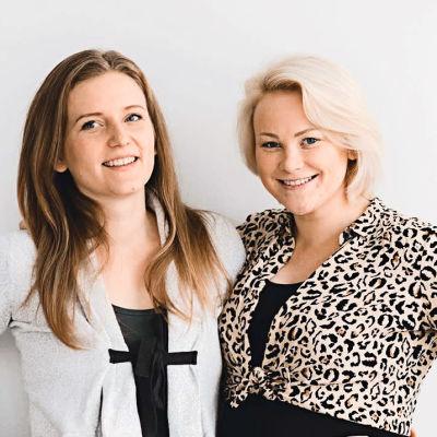 Två kvinnor står och håller om varandra och ler. De är båda gravida.