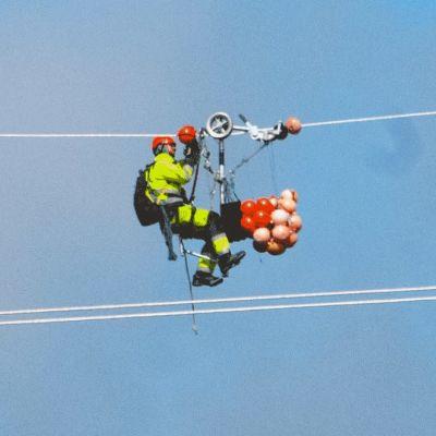 En servicearbetare hänger i en högspänningsledning.