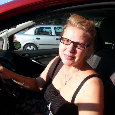 Nainen istuu auton ratissa.
