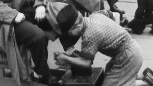 Poika kiillottaa kenkiä