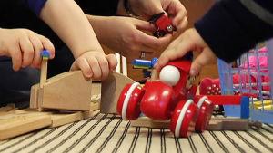 småbarnshänder och en vucen kvinnas händer som leker på golvet med träbilar.