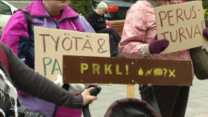 Folk står med plakat och demonstrerar jobb och socialskydd