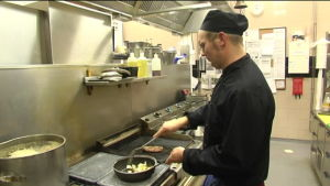 Man arbetar vid spisen i köket.