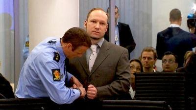 Polis öppnar Breiviks handbojor i rättegångssalen, åskådare tittar på.