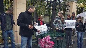 Demonstranter utanför Finlands ambassad med dockvagn i bur.