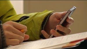 Ung med mobiltelefon i handen.
