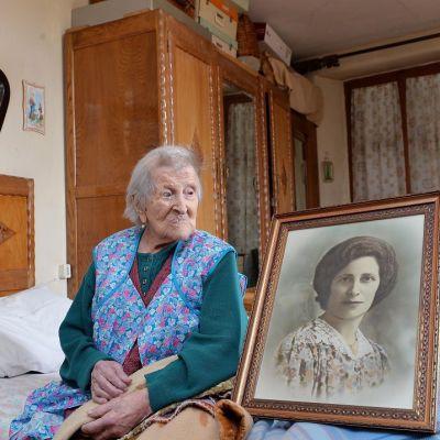 Emma Morano istuu sängyllä ja katsoo kuvaa, joka esittää häntä nuorena Verbaniassa, Pohjois-Italiassa.