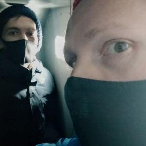 Aleksej Nazarov och Nikolaj Sjerbakov när de sitter inne i en av polisens bilar. På bilden har de mössa och munskydd.