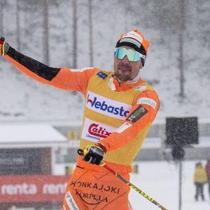 Ristomatti Hakola glidandes på skidor med ena staven i luften.