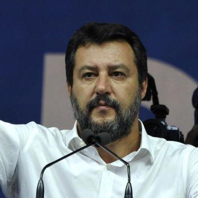 Matteo Salvini håller tal och sträcker ut handen.