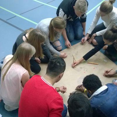 Elever som tillsammans ritar på ett stort papper.