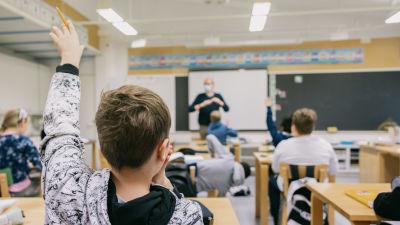 Oppilas viittaa tunnilla.