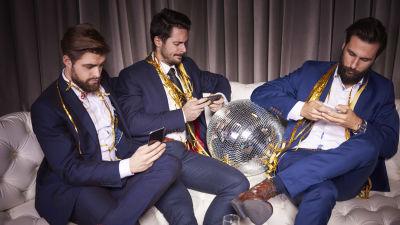 Tre män i stiliga kostymer sitter i soffa och ser på sina telefoner