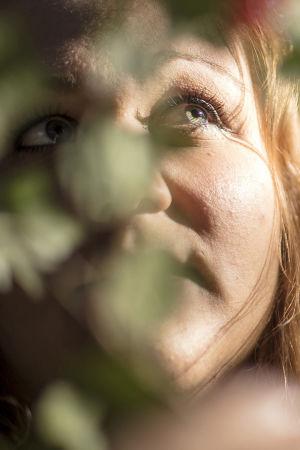 Riia Puska metsässä, katsoo yläviistoon, etualalla värikkäitä lehtiä epätarkkana.