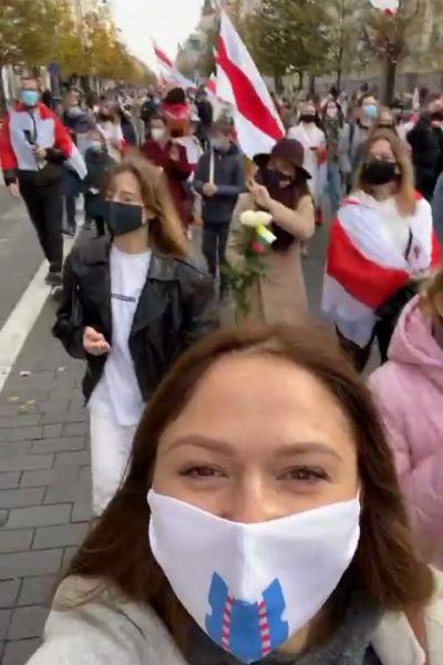 En kvinna med munskydd framför en protestmarsch