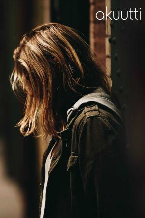 Nainen seisoo apeana vasten seinää.