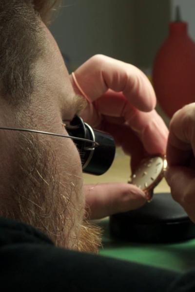 Närbild av en en urmakare som reparerar en klocka