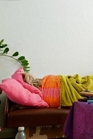 Ihminen makaa sohvalla sekaisessa asunnossa.