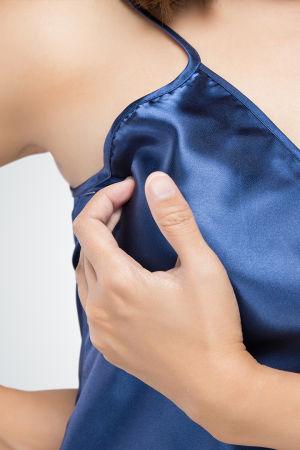 Nainen tunnustelee toista rintaansa. Kuvassa näkyy vain kädet ja rintakehä, kaikki muu on rajattu pois. Naisella on yllään sininen toppi.