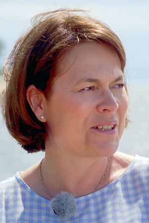 Martina Harms-Aalto sitter på soliga klippor vid ett sommarvarmt hav.