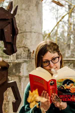 Kaisa Pulakka lukee romaania Tuulen viemää kartanon patiolla