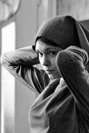 Mustavalkoisessa kuvassa nainen, joka laittaa päähänsä huivia.
