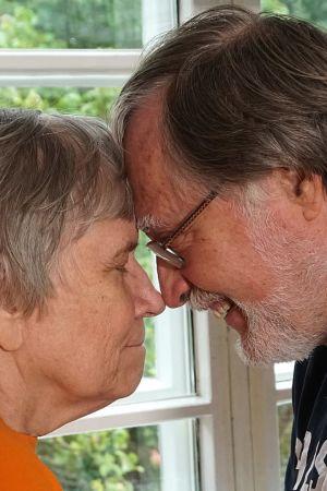Ett äldre par håller om varandra och håller ihop sina pannor.