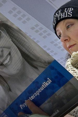 Nainen lukee Helsingin psykoterapiainstituutin esitettä.