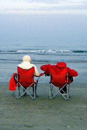 Kaksi ihmistä rantatuoleissa meren rannalla.
