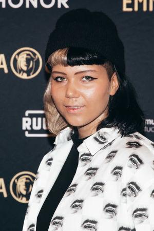 Vesta Emma-gaalan kuvausseinän edessä pipo päässä ja valkomustakuviollinen paita päällään.