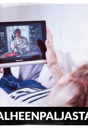 Eläkeikäinen nainen makoilee sohvalla katsoen tablettia. Kuvassa teksti Valheenpaljastaja.