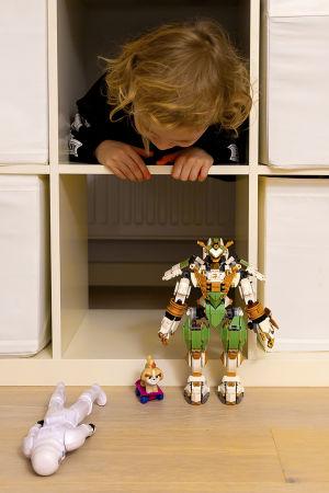 Kaapo-pikkupoika kurkistaa hyllystä, etualalla lego-ukko
