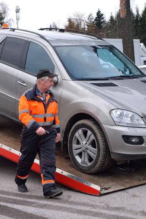 Vardagshjälten Nalle HIndsberg tar ner en bil från flaket.