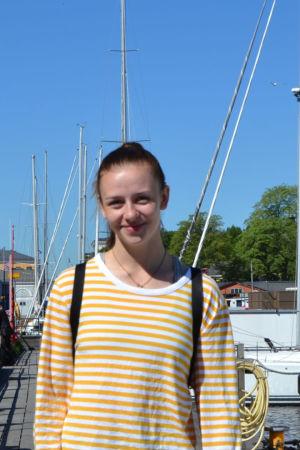 Emmy Nyström vid en strand framför några båtar.