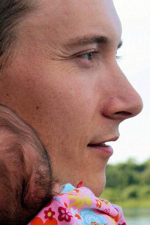 Nuori isä vauva olkapäällään